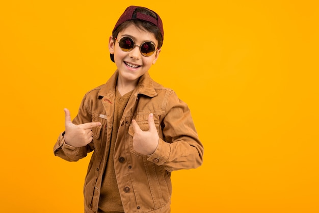 Menino adolescente europeu em uma jaqueta jeans marrom elegante casual e óculos elegantes mostra-se com a mão sobre um fundo amarelo com espaço de cópia.
