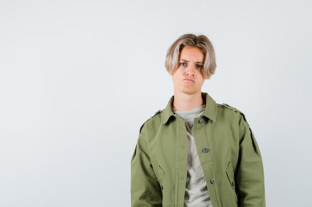 Menino adolescente fazendo careta enquanto olha para a câmera em uma camiseta