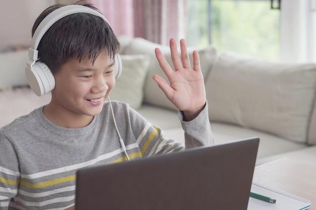Menino adolescente fazendo videochamada com laptop em casa, ensino doméstico, aprendendo conceito remotamente