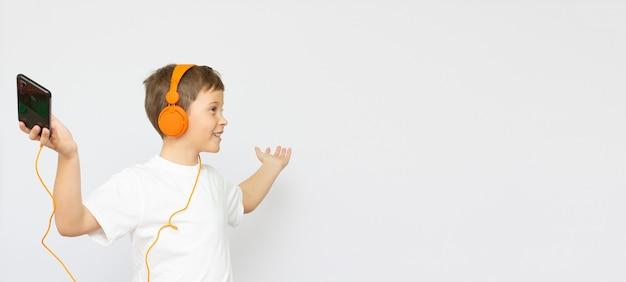 Menino adolescente feliz com fones de ouvido, isolado no branco
