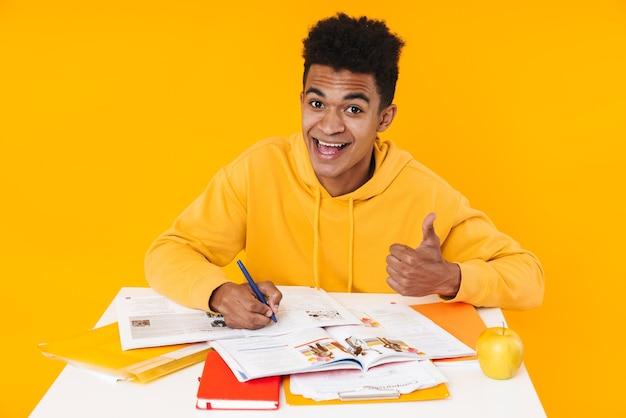 Menino adolescente feliz, estudando enquanto está sentado na mesa e escrevendo no livro isolado na parede amarela, mostrando os polegares para cima