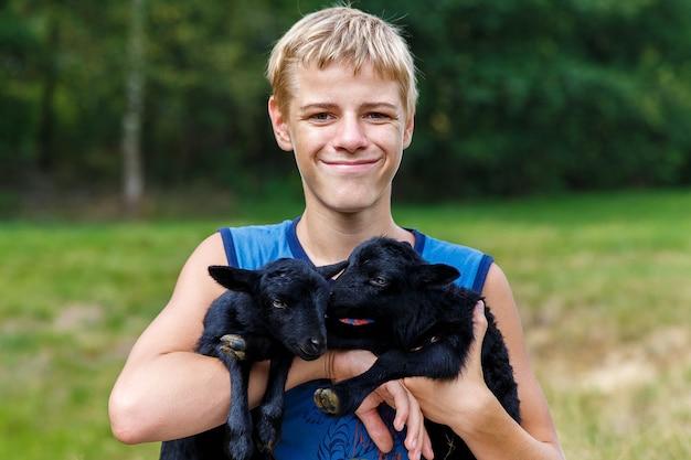 Menino adolescente feliz segurando cabrinhas pretas no prado.