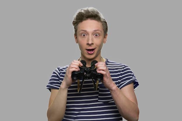 Menino adolescente feliz surpreso segurando binóculos. menino chocado com binóculos em fundo cinza.