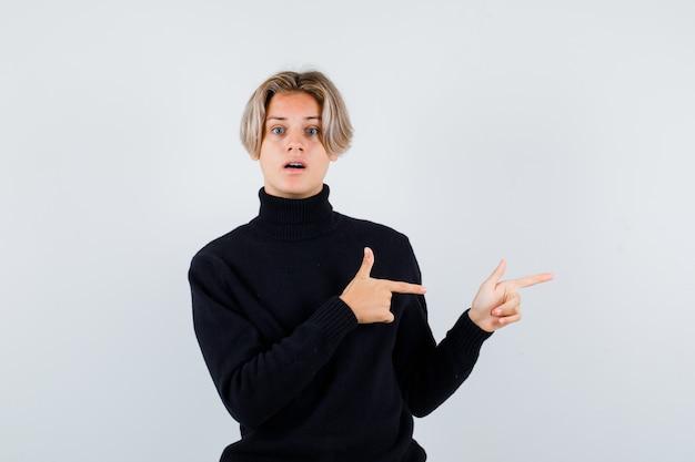 Menino adolescente fofo apontando para a direita com um suéter de gola alta e parecendo perplexo