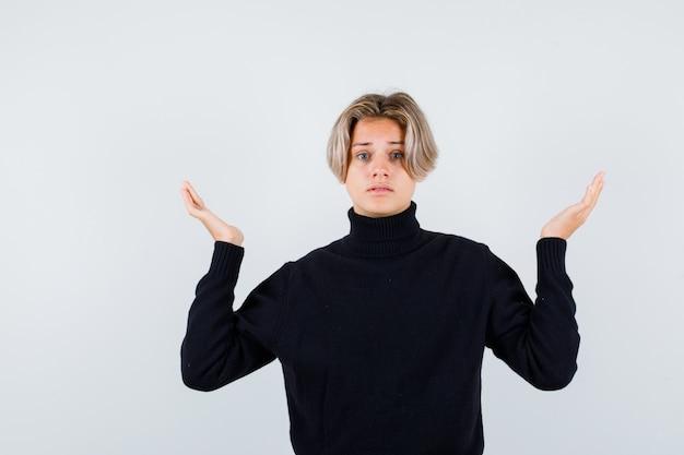 Menino adolescente fofo com um suéter de gola alta, mostrando um gesto de impotência e parecendo perplexo