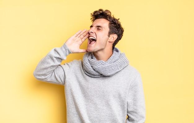 Menino adolescente gritando alto e com raiva para copiar o espaço ao lado, com a mão perto da boca