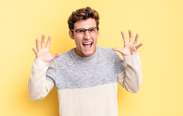 Menino adolescente gritando em pânico ou raiva, chocado, apavorado ou furioso, com as mãos perto da cabeça