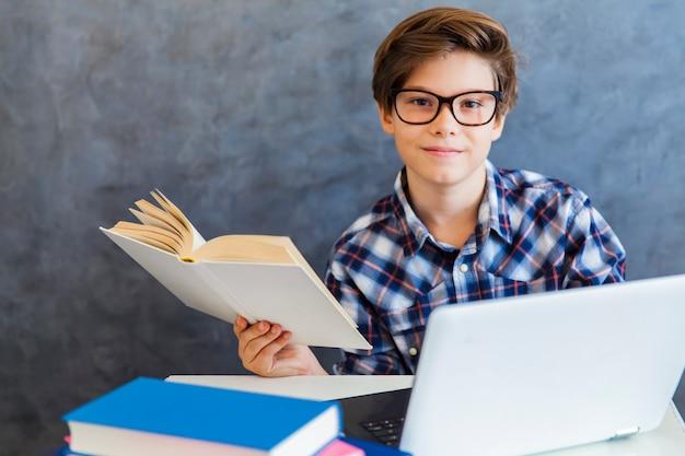 Menino adolescente lendo livro e usar o laptop em casa