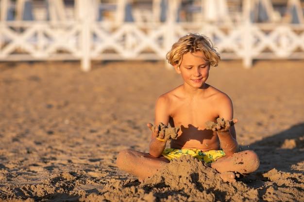Menino adolescente loiro bonito em shorts de banho amarelos, sentado na praia de areia e brincando com a areia contra a cerca branca do hotel. copie o espaço.