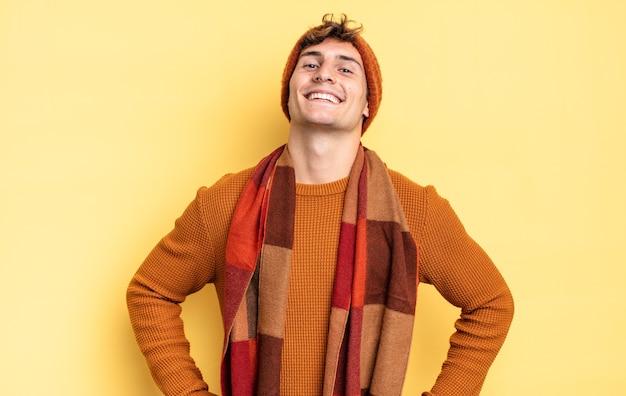 Menino adolescente parecendo feliz, alegre e confiante, sorrindo com orgulho e olhando para o lado com as duas mãos na cintura