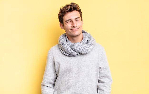 Menino adolescente parecendo feliz e amigável, sorrindo e piscando os olhos para você com uma atitude positiva