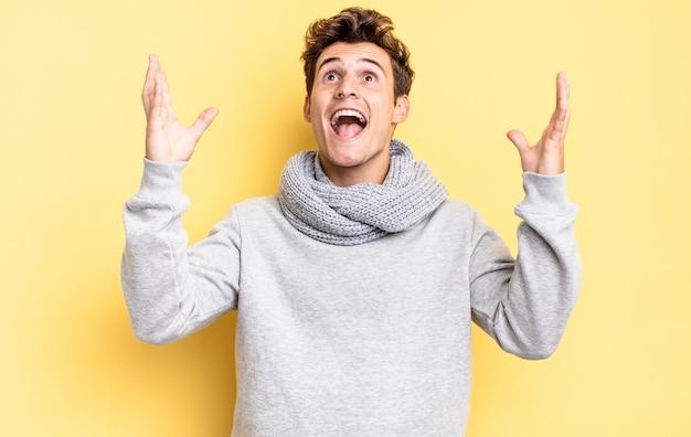 Menino adolescente se sentindo feliz, pasmo, sortudo e surpreso, comemorando a vitória com as duas mãos para cima