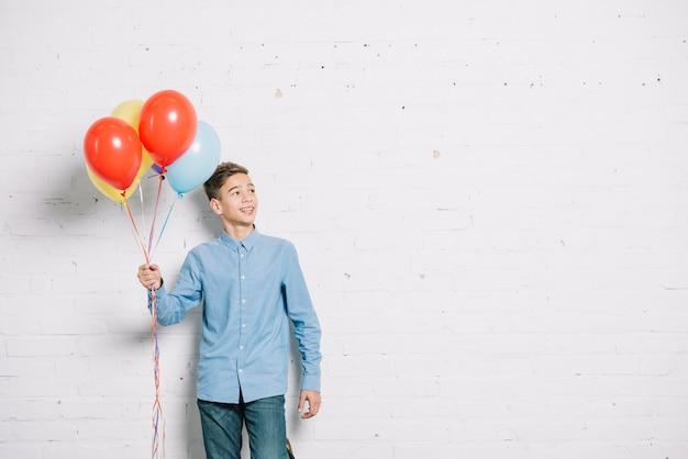 Menino adolescente, segurando, balões, em, mão, olhando