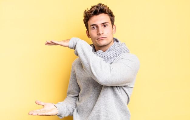 Menino adolescente segurando um objeto com as duas mãos no espaço lateral de cópia, mostrando, oferecendo ou anunciando um objeto