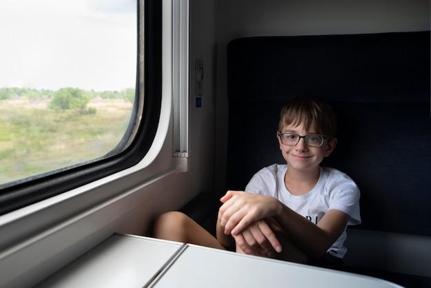 Menino adolescente sentado no vagão do compartimento