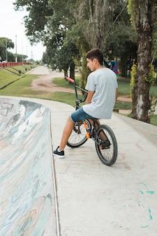 Menino adolescente, sentando, ligado, bicicleta, sobre, a, concreto, parque patim