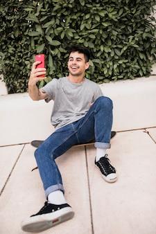 Menino adolescente, sentando, ligado, skateboard, levando, selfie, com, telefone móvel
