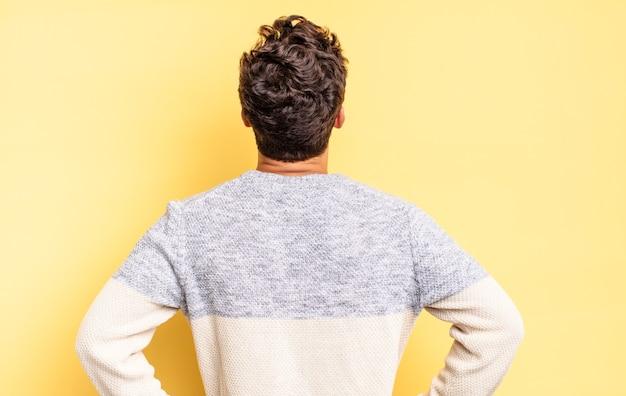 Menino adolescente sentindo-se confuso ou cheio ou dúvidas e perguntas, imaginando, com as mãos nos quadris, vista traseira