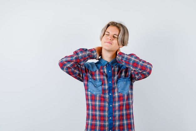 Menino adolescente sofrendo de dor no pescoço em uma camisa quadriculada e parecendo dolorido. vista frontal.