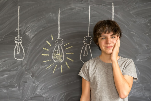 Menino adolescente sorridente tentando ter uma ideia