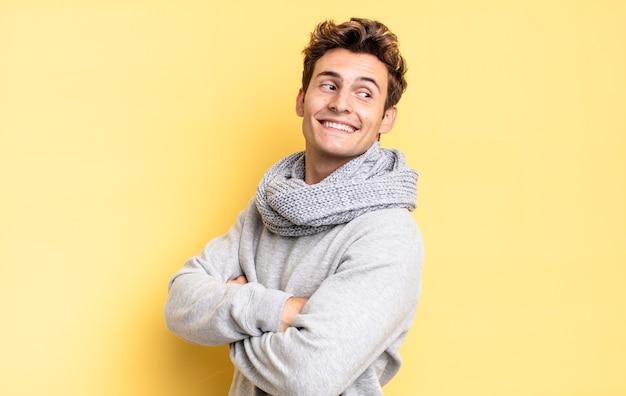 Menino adolescente sorrindo alegremente, sentindo-se feliz, satisfeito e relaxado, com os braços cruzados e olhando para o lado