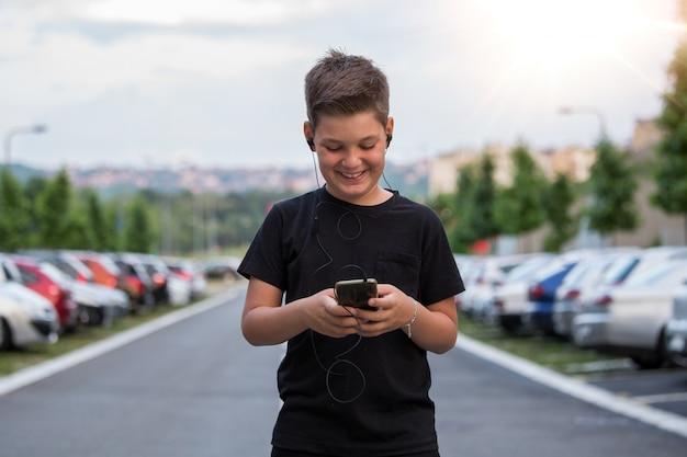 Menino adolescente, sorrindo, enquanto, texting, seu, amigos, através, redes sociais, usando, telefone móvel, sentando, contra, paisagem urbana