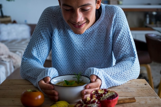 Menino adolescente sorrindo olhando uma sopa de legumes em casa na hora do almoço - estilo de vida de conceito de nutrição alimentar vegetariana e saudável - menino e cores de outono internas