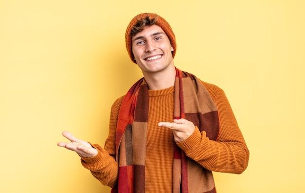Menino adolescente sorrindo, sentindo-se feliz, despreocupado e satisfeito, apontando para um conceito ou ideia no espaço da cópia ao lado