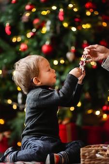 Menino adorável brincando com brinquedos de natal