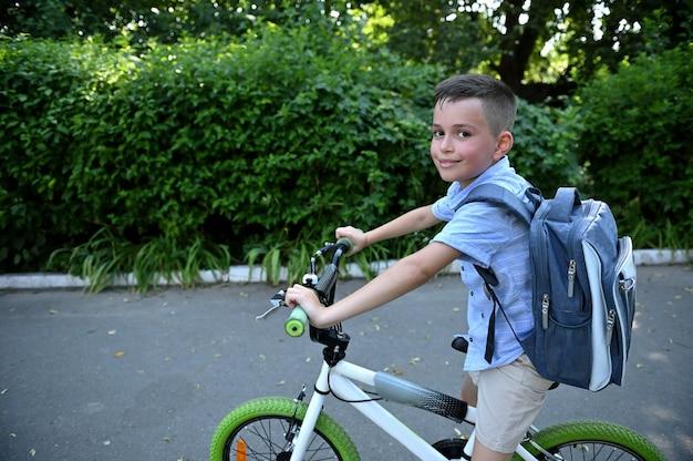 Menino adorável criança com bolsa escola, andando de bicicleta sorrisos bonitos olhando para a câmera. conceito de volta às aulas