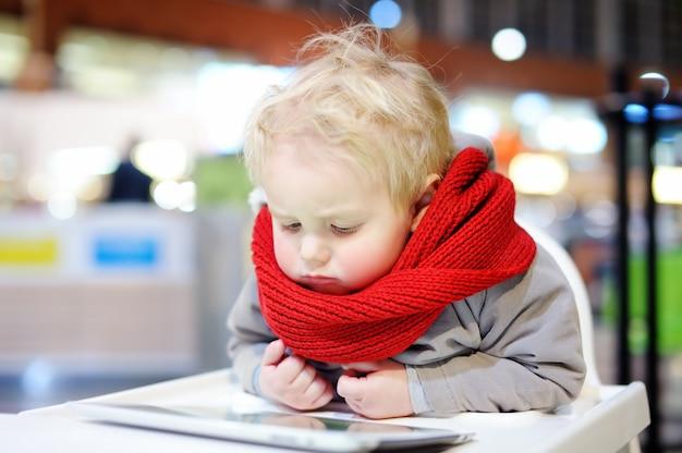 Menino adorável criança loira brincando com um tablet digital dentro de casa