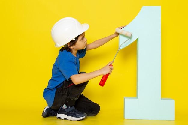 Menino adorável de camiseta azul e figura de número de pintura de capacete branco na parede amarela
