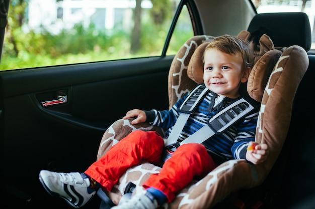 Menino adorável na cadeirinha de segurança
