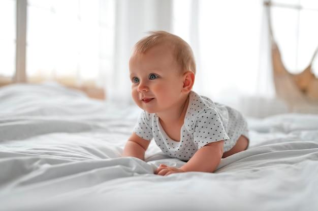 Menino adorável no quarto branco ensolarado. criança recém-nascida relaxando na cama. berçário para crianças pequenas. têxtil e roupa de cama para crianças. manhã em família em casa. criança recém-nascida durante o tempo de barriga.