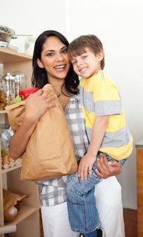 Menino adorável que desembala saco de mercearia com sua mãe