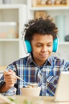 Menino africano com fones de ouvido assistindo algo no tablet pc enquanto toma café da manhã em casa