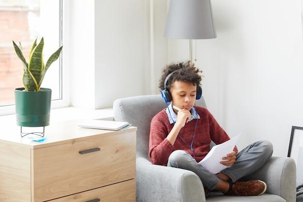 Menino africano com fones de ouvido sentado na poltrona e aprendendo a ler um livro na sala de casa