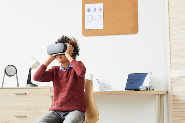 Menino africano com óculos de realidade virtual sentado na cadeira e curtindo o jogo virtual depois das aulas em casa