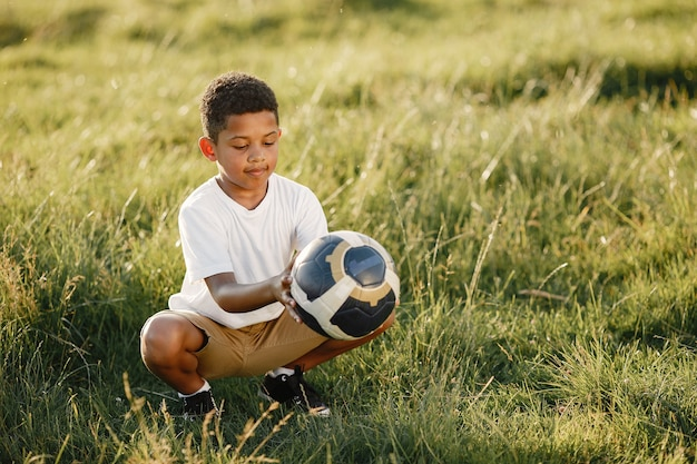 Menino africano. criança em um parque de verão. criança com bola de futebol.