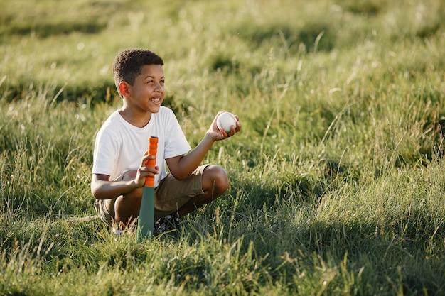 Menino africano. criança em um parque de verão. criança joga futebol americano.