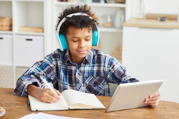 Menino africano em fones de ouvido usando tablet digital e fazendo anotações em seu caderno enquanto está sentado à mesa em casa