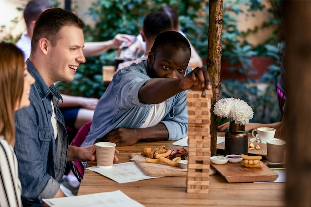 Menino africano está jogando jenga de jogo de mesa com os melhores amigos caucasianos no acolhedor restaurante local