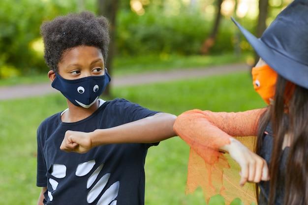Menino africano fantasiado brincando com seu amigo no parque ao ar livre