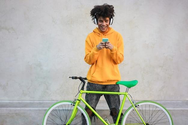 Menino africano feliz da geração do milênio com bicicleta ouvindo música com fones de ouvido ao ar livre - foco no aplicativo de rosto