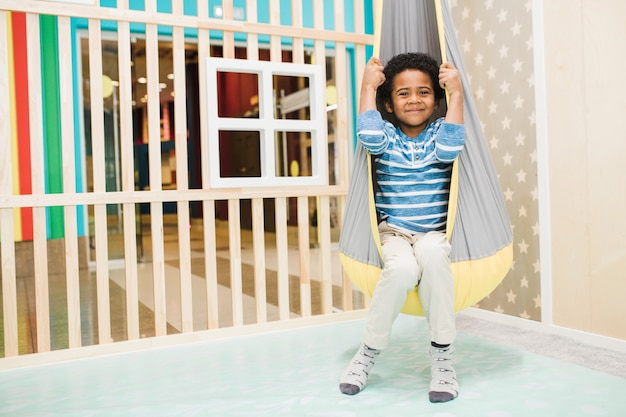 Menino africano feliz em trajes casuais sentado em uma rede pendurada no teto na área de recreação do centro de lazer