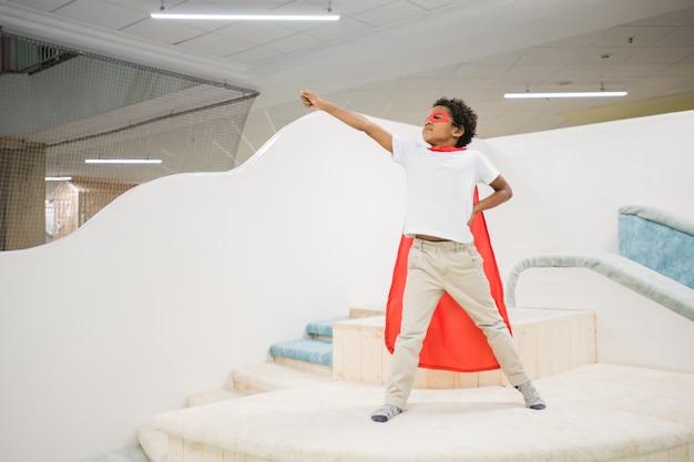 Menino africano fofo com um manto vermelho de super-herói e roupa casual branca esticando o braço enquanto brinca sozinho