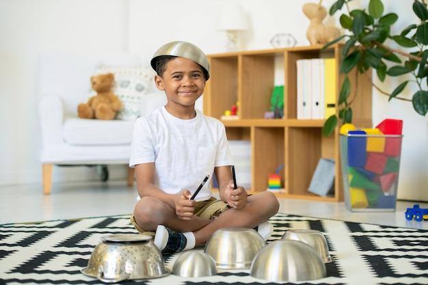 Menino africano fofo e engraçado com uma tigela metálica na cabeça e dois marcadores de texto nas mãos, sentado no chão e fazendo música