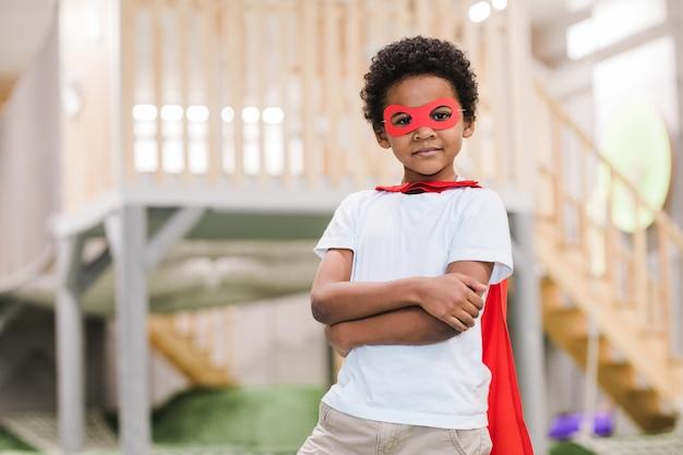 Menino africano fofo em trajes casuais brancos e manto vermelho de super-homem olhando para você enquanto brinca no jardim de infância