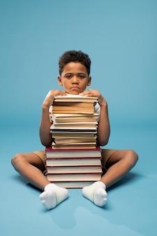 Menino africano infeliz de idade elementar sentado no chão com uma pilha alta de livros na frente e mantendo o queixo em cima dela