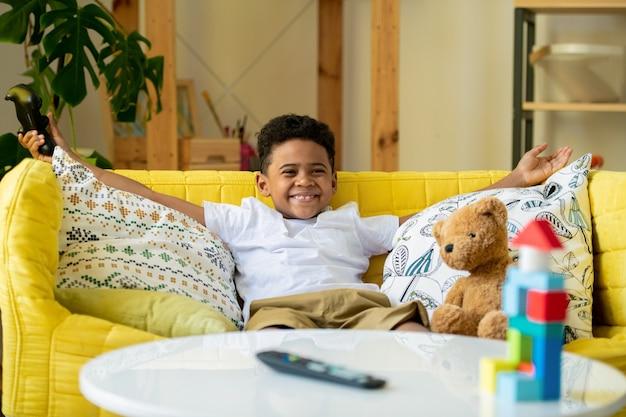 Menino africano ou mestiço com joystick olhando para a tela da tv enquanto está sentado no sofá amarelo à mesa e jogando videogame